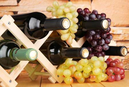 bordeau: Bottles of wine placed on wooden stand on stone wall background