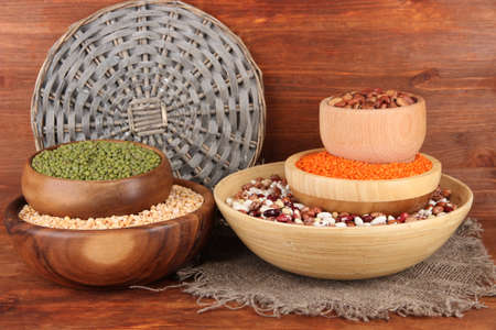 Different kinds of beans in bowls on wooden background photo