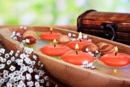 swimming candles: Beautiful candles in water on wooden table on natural background