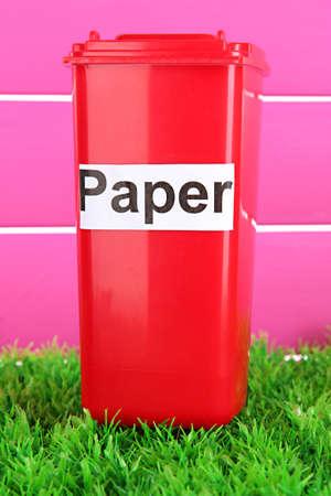 segregate: Recycling bin on grass on pink background