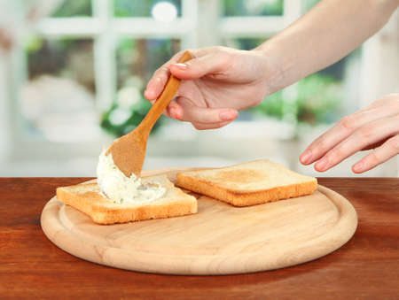 smears: Process of preparing salami rolls on roasted bread ,on bright background: female hand smears cheese cream on roasted bread
