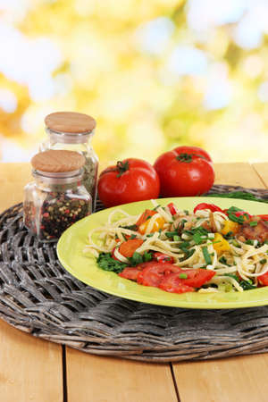 Noodles with vegetables in plates on bright background photo