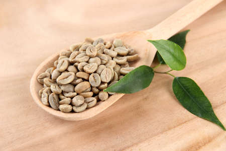 unroasted: Green coffee beans in spoon and leaves on wooden background Stock Photo