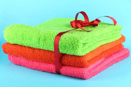 orange washcloth: Towels tied with ribbon on light blue background
