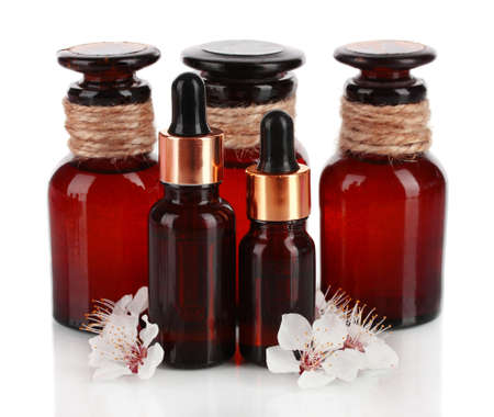 Aroma oils with flowers isolated on white photo