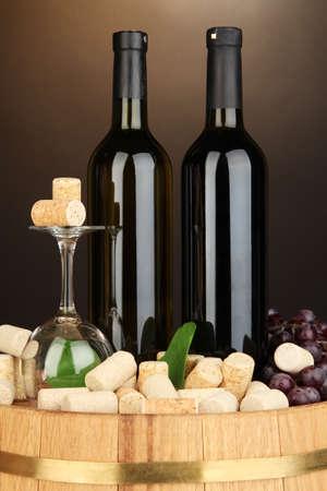 degustation: Wine and corks on barrel on brown background
