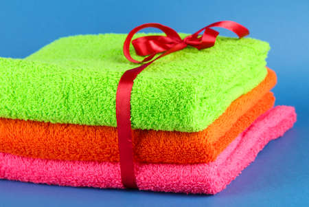 Towels tied with ribbon on blue background