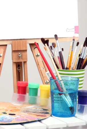 Wooden easel with clean paper and art supplies in room photo