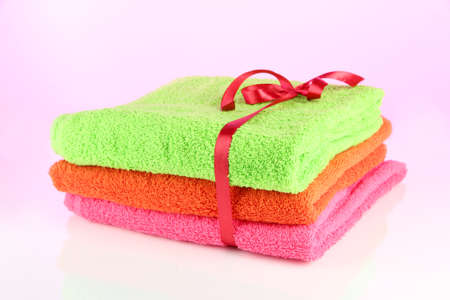 orange washcloth: Towels tied with ribbon on light pink background