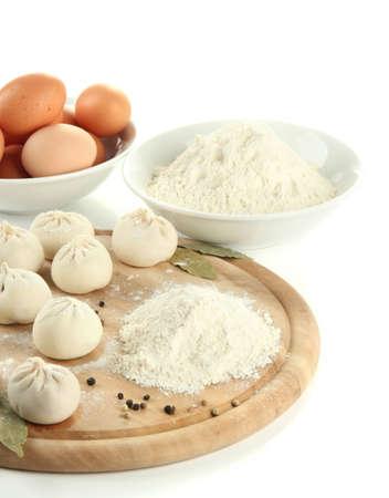 semifinished: Raw Georgian khinkali and ingredients on wooden desk, isolated on white