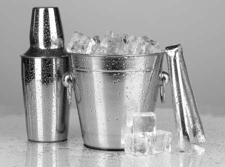 Metal ice bucket and shaker on grey background photo