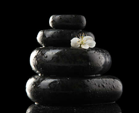 Spa stones and white flowers isolated on black photo