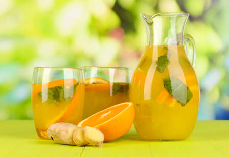Orange lemonade in pitcher and glasses on wooden table on natural background Stock Photo - 20784471