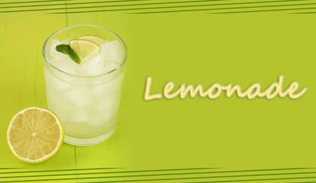 Lemonade in glass on green wooden background photo
