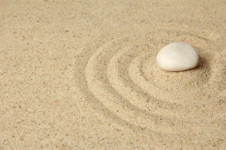 Zen garden with raked sand and stone close up photo