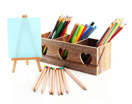 Different pencils in wooden crate and easel, isolated on white photo