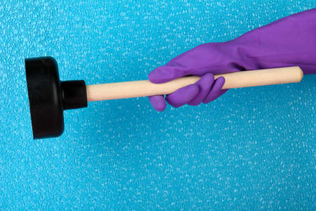 airtight: Toilet plunger in hand on blue background