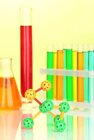 Molecule model and test tubes with colorful liquids on yellow background photo