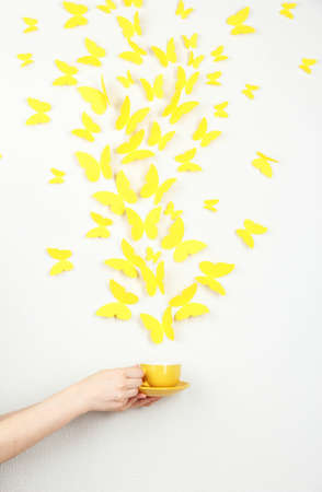 Paper yellow butterflies fly out of cup photo