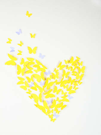 Paper yellow butterfly in form of heart on wall