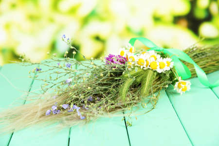 Bouquet of wild flowers and herbs, on wooden table on bright background photo