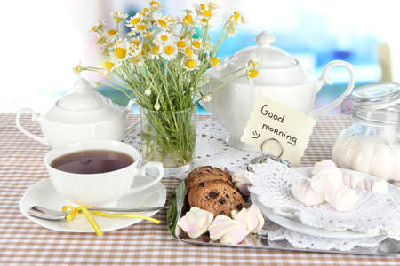 booked: Table setting with chamomiles on wooden table on window background