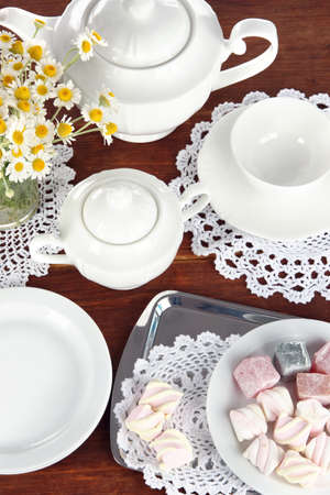 Table setting with chamomiles on wooden table photo
