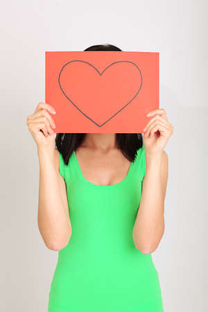 Young woman holding red painted heart on grey background photo