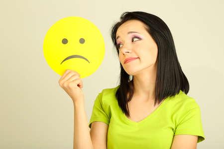 femme triste: Jeune femme tenant le papier avec smiley triste sur fond gris Banque d'images