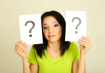 Woman with question marks on grey background photo