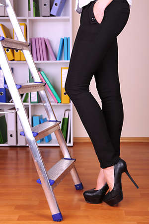 Woman climbing up ladder in office