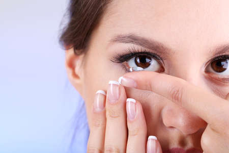 Young woman putting contact lens in her eye close up photo