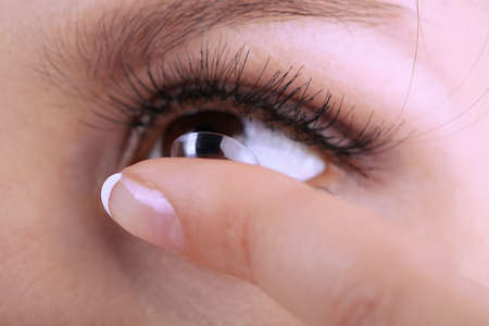 nearsighted: Young woman putting contact lens in her eye close up Stock Photo