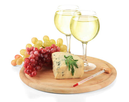 Glasses of wine, tasty blue cheese and grape on cutting board, isolated on white photo
