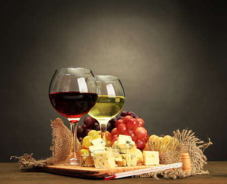 food table: Composition with wine, blue cheese and grape on wooden table, on grey background