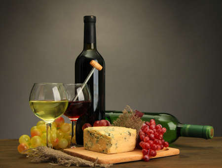Composition with wine, blue cheese and grape on wooden table, on grey background photo