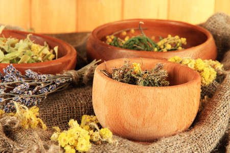 bagging: Medicinal Herbs in wooden bowls on bagging on table close-up