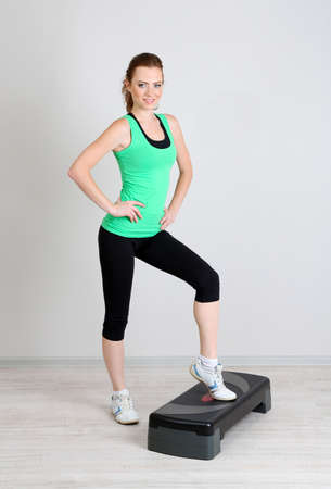 Beautiful young woman exercises on stepper photo