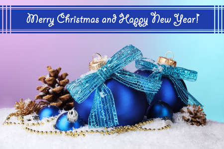 Beautiful blue Christmas balls and cones on snow on bright background photo