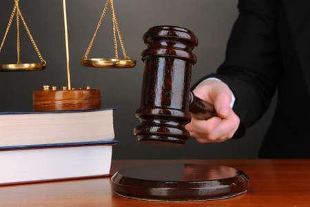 martillo juez: Mazo del juez en la mano sobre fondo gris Foto de archivo
