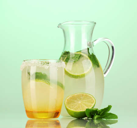 Lemonade in pitcher and glass on turquoise background photo