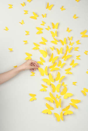 Paper yellow butterflies fly on wall in different directions photo