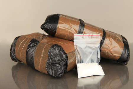 drug deals: Packages of  narcotics on gray background