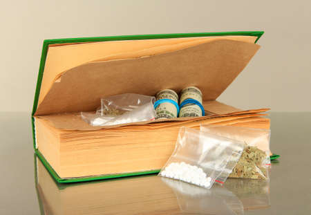 Narcotics in book-hiding place on gray background photo