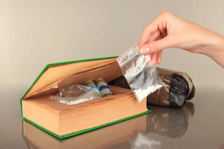 Hand holding narcotics near book-hiding place on gray background photo