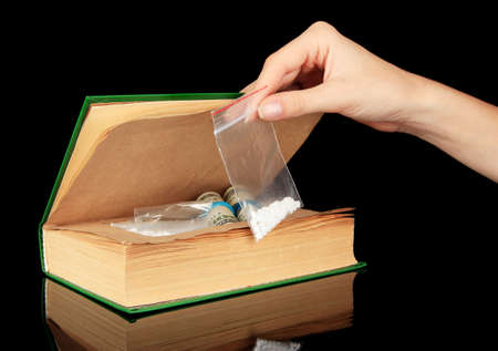 Hand holding narcotics near book-hiding place isolated on black photo