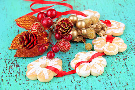 Christmas cookies and decorations on color wooden background photo