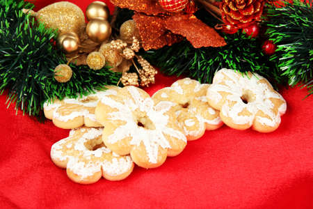Christmas cookies and decorations on color fabric background photo