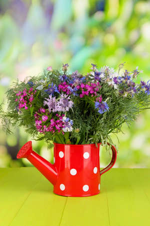 Beautiful bouquet in watering can on wooden table on natural background photo