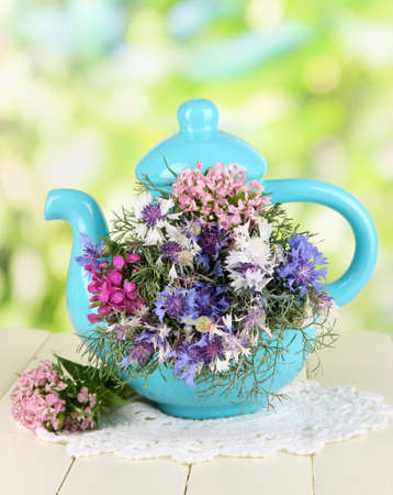 Beautiful bouquet in blue teapot on wooden table on natural background Stock Photo - 20830902